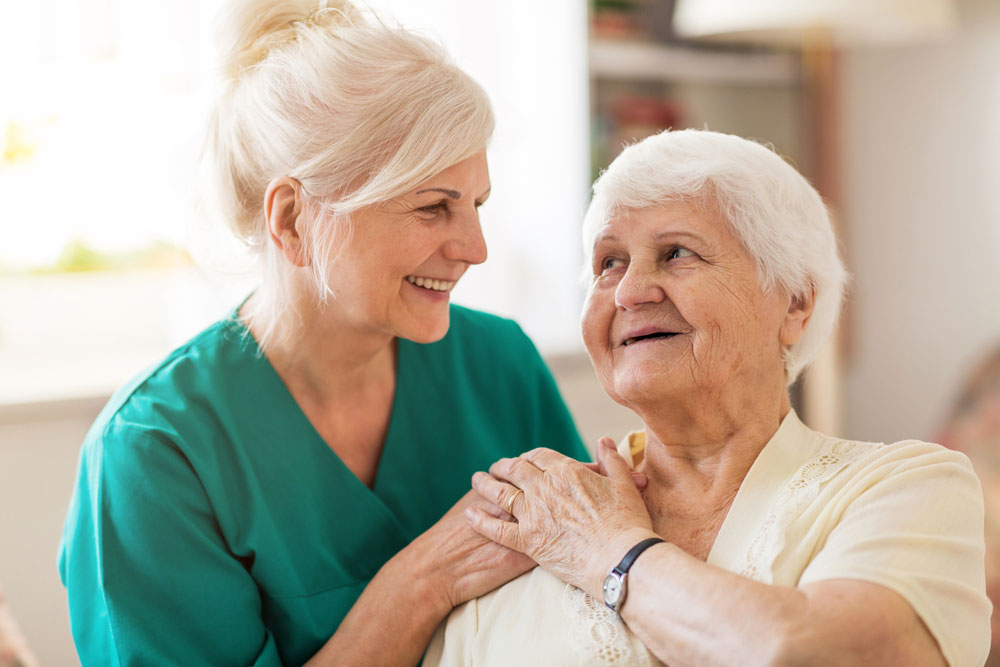 nurse comforting older woman